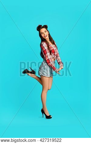 Full Length Portrait Of Pretty Pinup Lady In Vintage Style Outfit Lifting Leg, Being Flirty On Blue