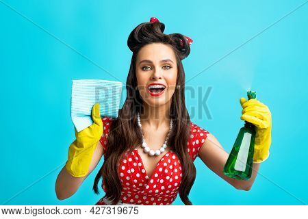 Cheerful Pinup Lady In Retro Style Wear Doing Cleanup With Rag And Spray Detergent On Blue Studio Ba