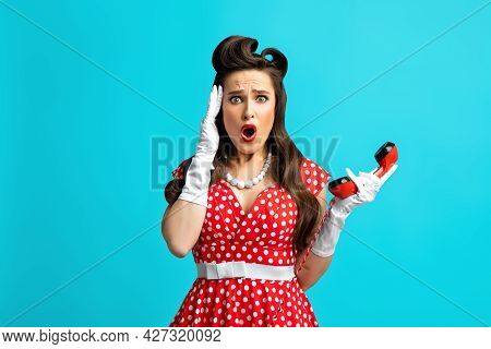 Terrified Millennial Woman In Retro Pinup Dress Holding Landline Phone Receiver, Touching Her Temple