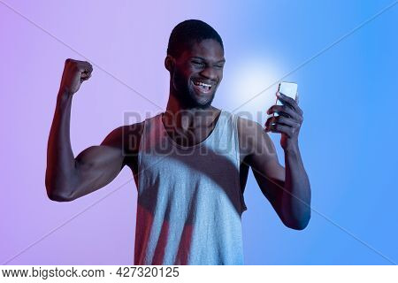 Excited Black Guy With Smartphone Making Yes Gesture, Winning Sports Bet In Neon Light