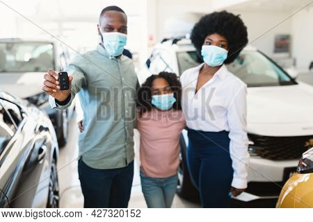 Young Black Family In Face Masks Holding Car Key At Automobile Dealership, Selective Focus