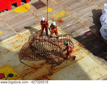 Worker is on the supply boat transfer cargo to oil and gas industry and moving cargo from the boat t