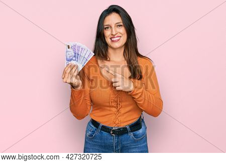 Beautiful hispanic woman holding 20 swedish krona banknotes smiling happy pointing with hand and finger