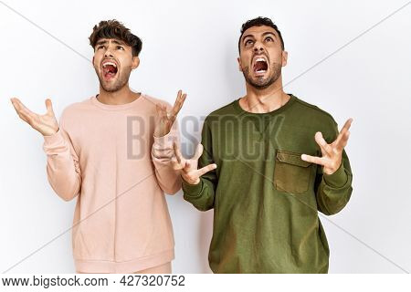 Young gay couple standing over isolated white background crazy and mad shouting and yelling with aggressive expression and arms raised. frustration concept.