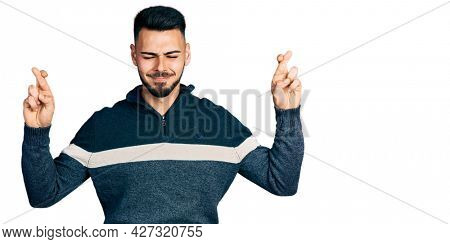 Young hispanic man with beard wearing casual winter sweater gesturing finger crossed smiling with hope and eyes closed. luck and superstitious concept.