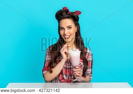 Portrait Of Sexy Pinup Woman In Retro Style Outfit Drinking Milk Shake From Glass, Smiling At Camera