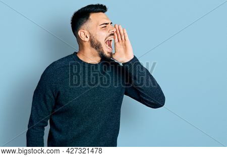 Young hispanic man with beard wearing casual winter sweater shouting and screaming loud to side with hand on mouth. communication concept.