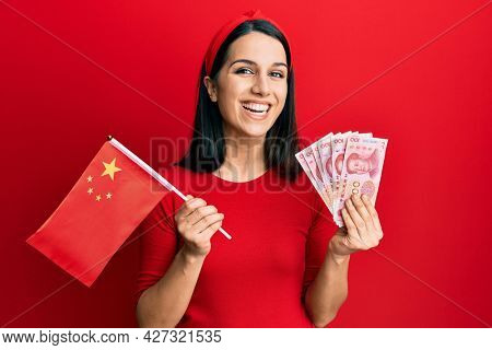 Young hispanic woman holding china flag and yuan banknotes smiling and laughing hard out loud because funny crazy joke.