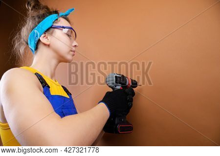 Young Woman Repairman In Overalls And Goggles Works With A Screwdriver In The Studio On A Brown Back