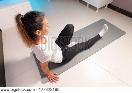 Sporty Slim Caucasian Woman Doing Self Massage On Fitness Mat With Massage Ball Indoors. Self-isolat