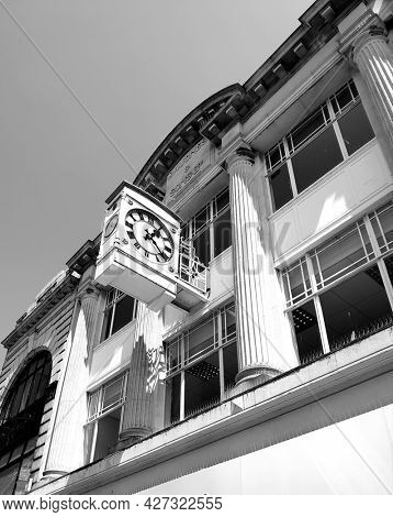 SOUTHEND ON SEA, UK - 19th July 2021: Historic 1890s store front and clock in Southend High Street, taken in black and white.