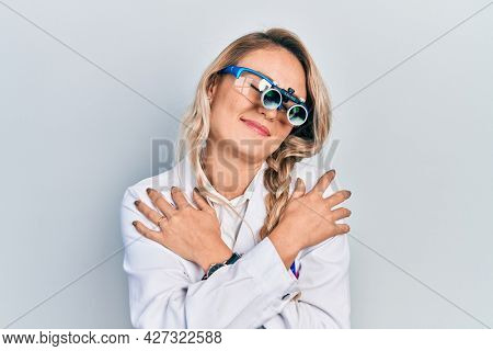 Beautiful young blonde woman wearing optometry glasses hugging oneself happy and positive, smiling confident. self love and self care