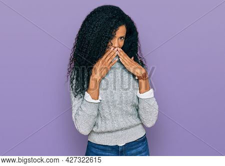 Middle age african american woman wearing casual clothes laughing and embarrassed giggle covering mouth with hands, gossip and scandal concept
