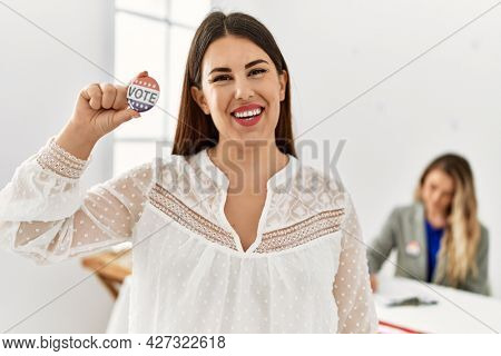 Young american voter woman holding i voted badge standing at electoral college.