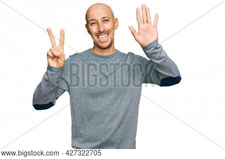 Bald man with beard wearing casual clothes showing and pointing up with fingers number seven while smiling confident and happy.