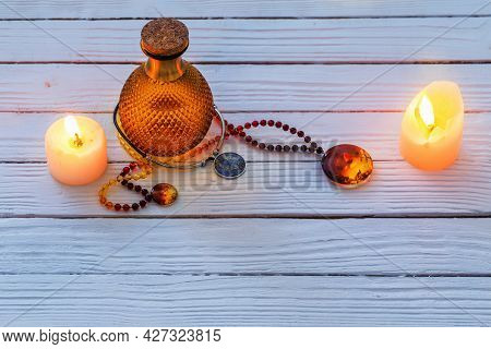 Magic Potion And Amber Necklace On Blue Wooden Background