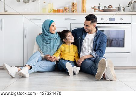 Portrait Of Happy Muslim Family With Little Daughter Sitting On Floor In Kitchen