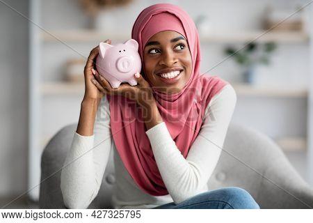 Islamic Savings Concept. Cheerful Black Muslim Woman In Hijab Holding Piggybank