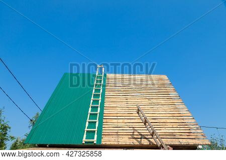 Construction Industry. Timber Framework Of Greenhouse Roof Trusses With Scaffold On A Building Being