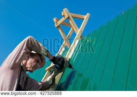 Construction Elderly Worker Install New Roof, Roofing Tools, Electric Drill Used On New Roofs With M