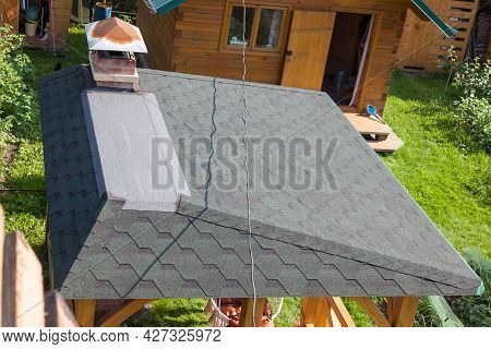 Modern Roofing And Decoration Of Chimneys. Flexible Bitumen Or Slate Shingles. House With A Roof Fro
