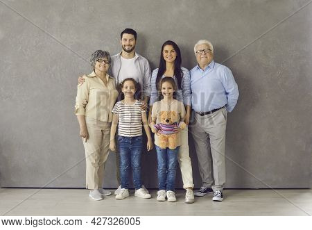 Studio Portrait Of Happy Multi Generational Family Standing Together And Smiling