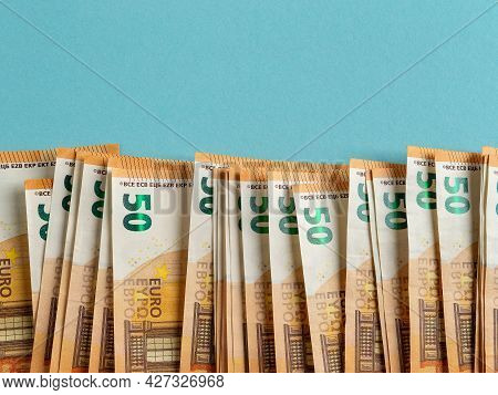 Orange 50 Euro Paper Banknotes In A Row Against Blue Background. Cash Savings And Wealth, Counting M