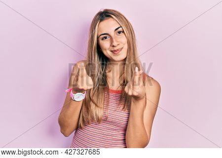 Beautiful hispanic woman wearing casual summer t shirt doing money gesture with hands, asking for salary payment, millionaire business