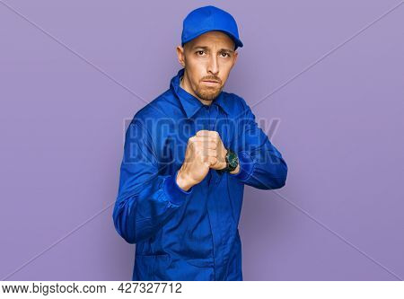 Bald man with beard wearing builder jumpsuit uniform ready to fight with fist defense gesture, angry and upset face, afraid of problem