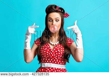 Beautiful Pinup Woman In Classic Outfit Blowing Bubble, Pointing At It On Blue Studio Background