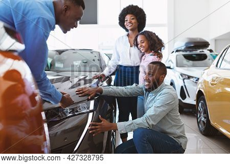 Happy Black Family Choosing New Car, Salesman Showing Them Luxury Auto At Automobile Dealership Stor