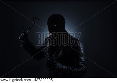 Man Wearing Knitted Balaclava With Crowbar On Black Background
