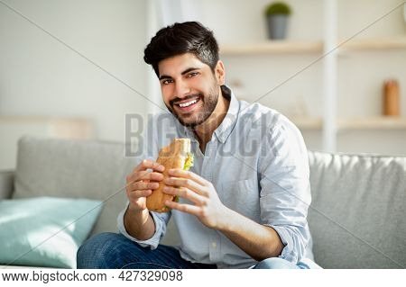 Cheat Meal Day. Happy Arab Man Eating Tasty Sandwich And Smiling To Camera, Sitting On Sofa In Livin