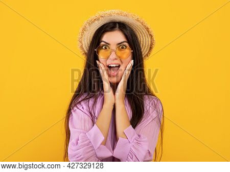 Overjoyed Armenian Lady In Stylish Summer Outfit Touching Her Face And Shouting Wow On Yellow Studio