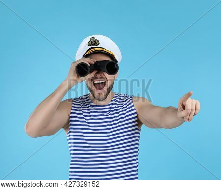 Sailor Looking Through Binoculars And Pointing On Light Blue Background