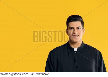 Priest Wearing Cassock With Clerical Collar On Yellow Background. Space For Text