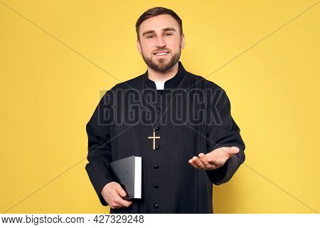 Priest In Cassock With Bible Reaching Out His Hand On Yellow Background