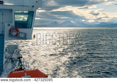 Cabin Of A Boat Sailing In The Sea By Lofoten Islands. Dramatic Clouds And Mountain Range On The Dis