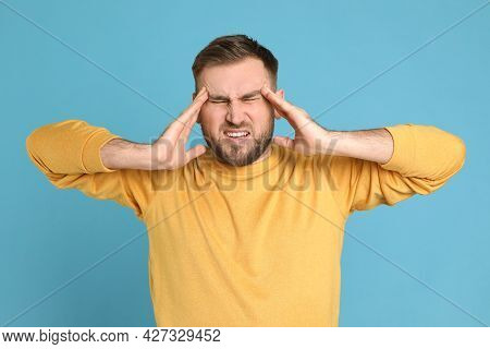 Man Suffering From Migraine On Light Blue Background
