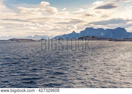 Stormclouds With Sun Shining Through Them Above Dramatic Mountain Range Of Lofoten Islands, Viewed F