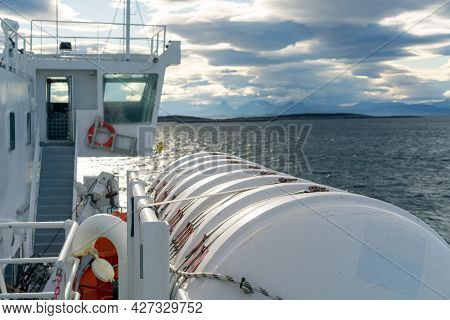 Big White Tank Attached To A Boat Sailing In The Sea By Lofoten Islands. Dramatic Clouds And Mountai