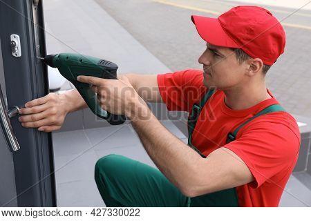 Handyman With Screw Gun Repairing Door Lock Outdoors
