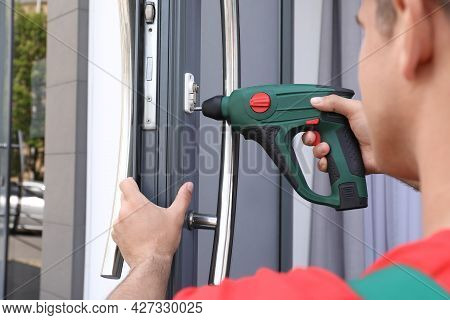 Handyman With Screw Gun Repairing Door Lock Outdoors, Closeup