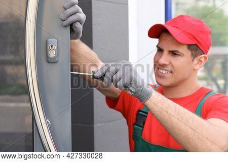 Handyman With Screwdriver Repairing Door Lock Outdoors