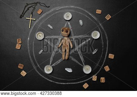 Voodoo Doll With Pins Surrounded By Ceremonial Items On Black Table, Flat Lay