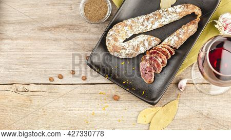 Sliced Duck Meat Salami Sausage On Black Dish With With The Ingredients Over Wooden Rustic Backgroun