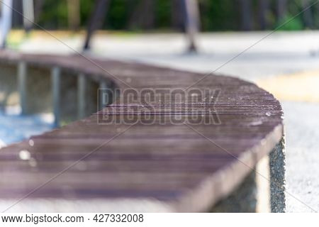 A Long Wooden Curved Bench In The Park On A Sunny Day With A Background Blur