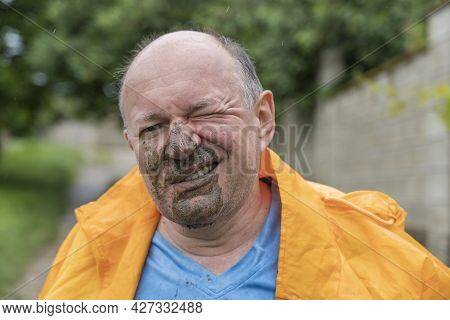 Portrait Of A Man With A Dirty Face After Falling Into A Puddle In The Rain, Close Up