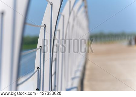 An Element Of A Tubular Metal, Curved, Horizontal Fence Of The River Embankment, A Sunny Day, The Ba