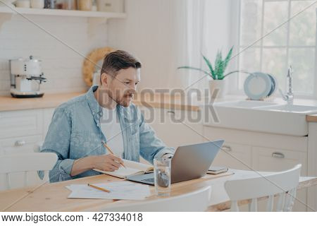 Portrait Of Concentrated Male Freelancer Working On Project Remotely From Home While Sitting At Kitc